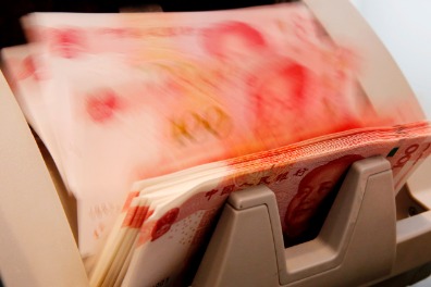 Chinese 100 yuan banknotes are seen in a counting machine while a clerk counts them at a branch of a commercial bank in Beijing, China, March 30, 2016.