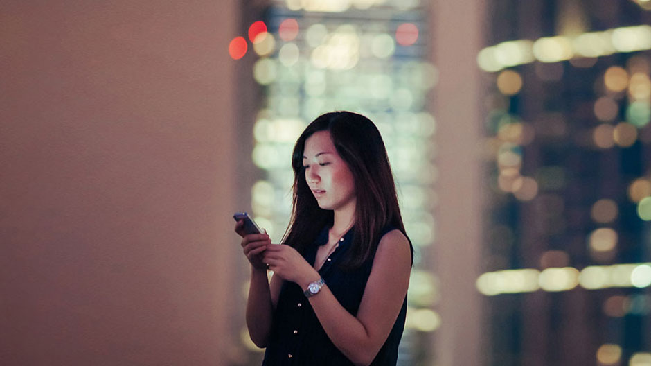 Young Asian female on smartphone in city at night