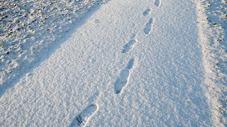 Footprints are seen on a snow covered path in a park in Knutsford, northern England, January 5, 2009.